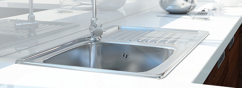 Stainless steel kitchen sink in white counter top