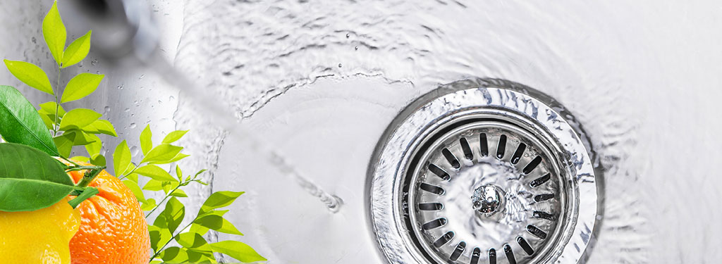Water flowing down stainless steel kitchen sink drain with orange and lemon fruit in the foreground