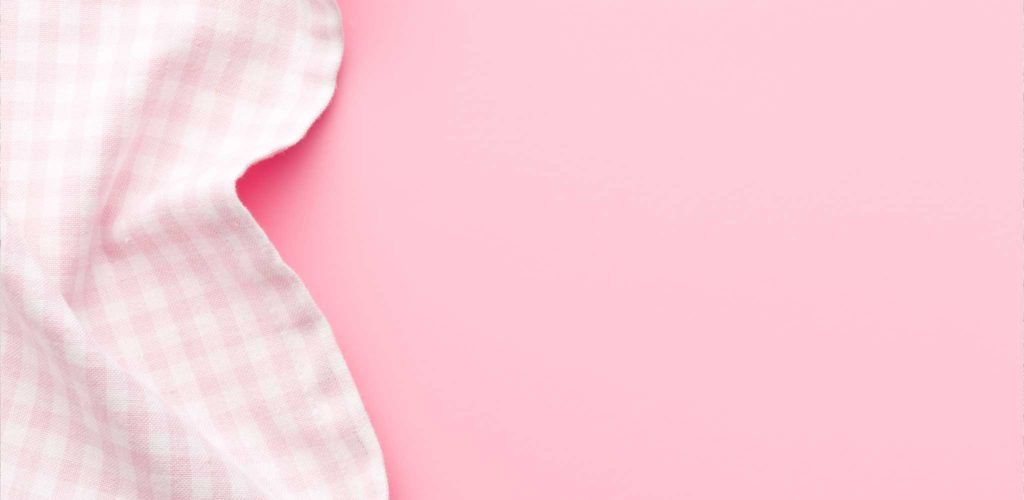 Pink gingham fabric over pink background - example application of woolite laundry products