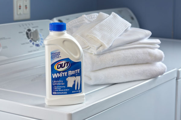 OUT White Brite laundry whitener with folded white laundry on washer